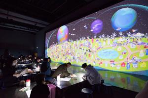 「3D お絵かきタウン」 まち(タウン)をつくる(車、ビルなど)と、UFOや宇宙船などの絵を描くと、目の前のスクリーンに3Dで出現し、動き出してまちができていく。自分たちで描いたまちは、触ることができ、車に触るとスピードが変わったりする。