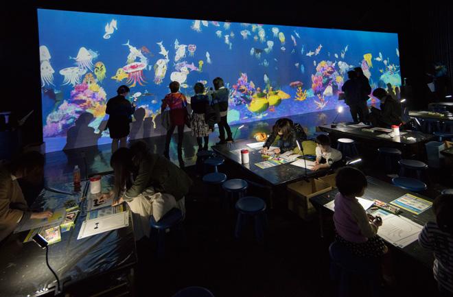 「お絵かき水族館」 紙に魚の絵を描くと、目の前の水族館でその魚たちが泳ぎ出す。自分たちの描いた魚に触ると、魚はいっせいに逃げ出し、エサ袋に触ると魚にエサをあげることもできる。