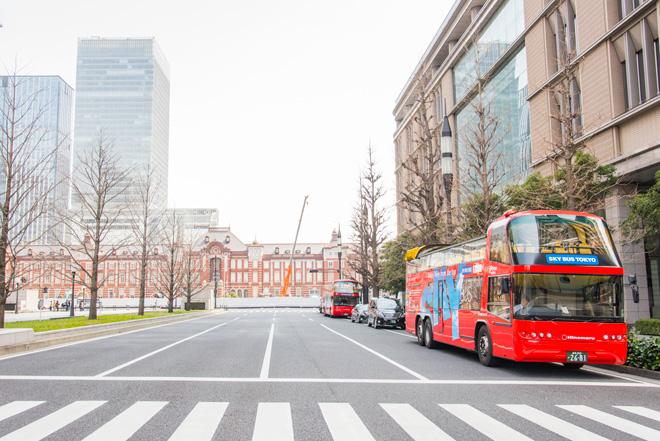 東京駅丸の内駅舎を背景に走行中のスカイバス。