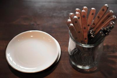カトラリーや取り皿がテーブルに。気取らないカジュアルさが心地いい。