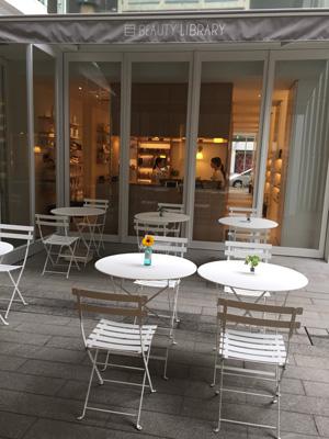 白いテーブルと椅子が並べられた中庭。ピラティスはこのスペースにヨガマットを敷いて行われる。