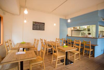 カフェのような明るい雰囲気。オープンキッチンも楽しい。 素朴なテーブルやイスが食堂のようで和ませてくれる。