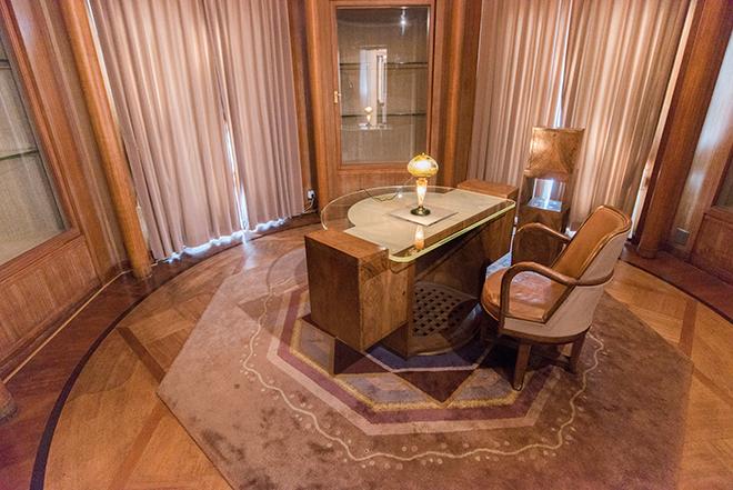 正方形の室内の四隅に作り付けられた飾り棚によって円形になった書斎。八角形の絨毯の上に置かれた机には、「波濤に魚文ランプ」(1902-1904年頃、北澤美術館蔵)が置かれています。