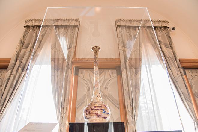 改修で復元された朝香宮殿下の居間の壁紙。カーテンと作品の形がシンメトリーをつくっています。「菊花文鶴頸大花瓶」(1900年頃) 北澤美術館蔵。