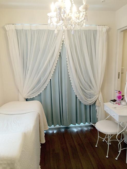白で統一した可愛らしい施術室は約13㎡。 ティファニーブルーのカーテンがアクセント。 友人宅に訪ねたようなプライベート感のある空間。