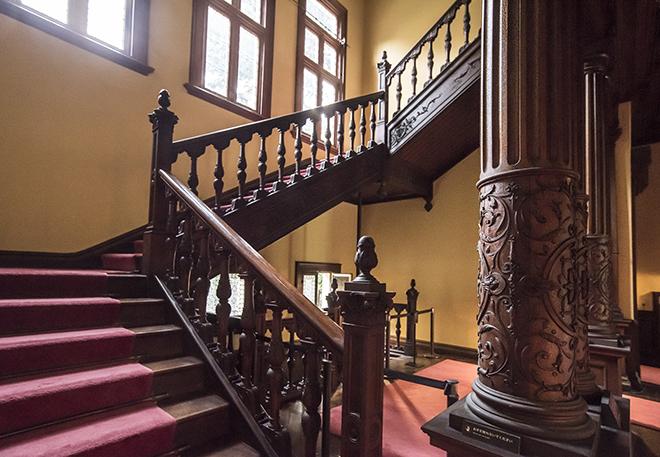 ゴシック様式の重みを持つ大階段の柱には、ジャコビアン様式の象徴であるツルを巻くような装飾が施されている。