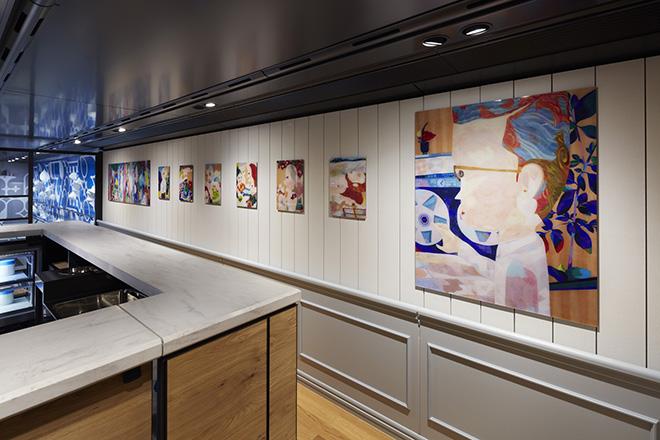 カフェスペースの壁面は、古武家賢太郎の色鉛筆画が飾られている。