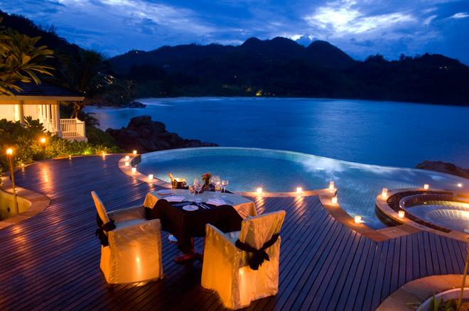 夕闇に染まっていく海と空を眺めながら、二人きりのディナータイム。キャンドルで灯されたプールが神秘的に浮かび上がる。