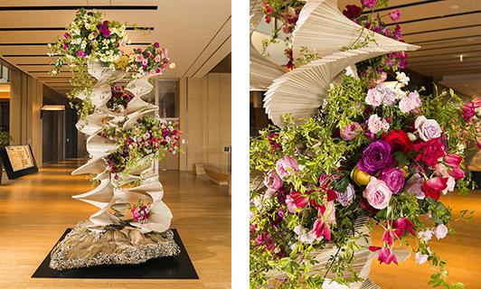 グランプリ『Blooming』/サンジョルディフラワーズ ザ・デコレーター 10周年を迎えた東京ミッドタウンの、時を積み重ねてますます咲き誇るイメージを、合板を重ねたらせん階段と上部に比重を置いたバラのアレンジメントで表現。躍動感、高揚感が感じられた。