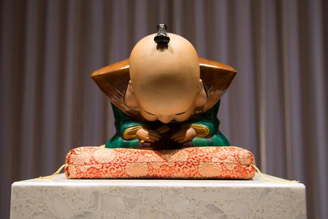 片山氏に代わりお辞儀をする福助人形が、来場者に足を運んでくれたことへのお礼として展覧会は完結する。