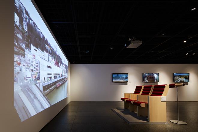 音楽ホールで使われるオリジナル座席の展示は座ることもできる。座面と背もたれが紙管で、周りに赤色のクッションを巻いてある。座って鑑賞できるのは、建設プロセスを定点カメラで記録した動画。(C) Nacása & Partners Inc.