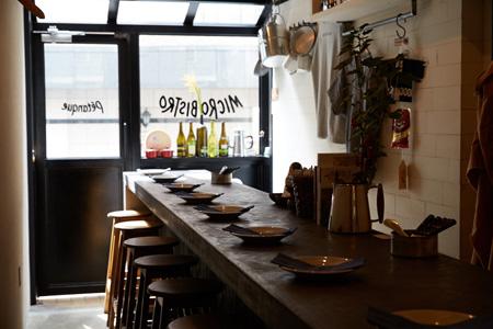 スケルトンの天井に温かみのある木製のカウンターやイスのバランスもカッコいい。