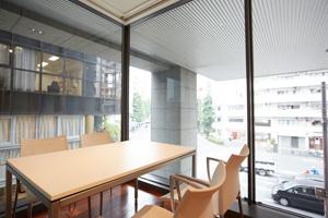 2階ラウンジのミーティング用のテーブルセット。明るいガラスファサードから代官山の街並みが見える。