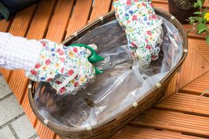 ▲ カゴを使うときは、ビニールなどを敷き、 はさみで水抜け用の穴をあける。