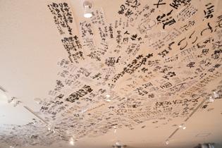 釜ヶ崎芸術大学の展示ブース。天井に貼られた労働者の方々の書が力強い。
