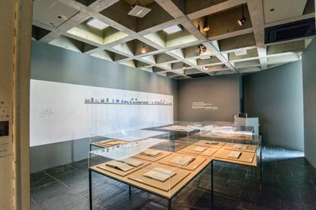 4階の会場には磯崎新氏の作品年表を展示。年代ごとに作品名と写真が詳細に記されている。