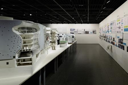 会場に入るとフロア中央に展示されている多くの模型。大きさや素材はさまざまで、多角的に検討されている様子が伝わってくる。 (C) Nacasa & Partners Inc.