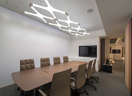 シンプルでありながらデザインされた「ミーティングルーム」。YAMAGIWAのオリジナルLEDモジュール「systemX LED versionL」を2列に連ねて室内を明るく照らし、無機質になりがちなミーティングルームをデザイン空間に変えている。