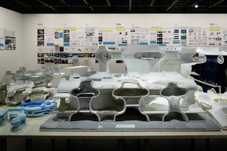 所狭しと置かれている模型とも関連しながら、壁には設計競技での提出資料などを多数紹介。構造、音響、空調などの検証が繰り返されたことが時系列で示されている。 (C) Nacasa & Partners Inc.