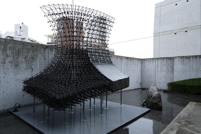 TOTOギャラリー・間の中庭に出ると、台中メトロポリタンオペラハウスの壁の一部を原寸大でつくったモックアップが置かれている。壁の厚さはほとんどが40cm。「カテノイド」という三次元に曲がった面でつくられる構造で、すさまじい量の鉄筋が高い密度で組まれた姿は圧巻。CGだけでは感じられない迫力を感じる。 (C) Nacása & Partners Inc.