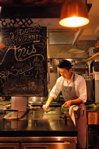 オープンキッチンの中央にある鉄板で調理する清水さん。